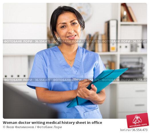 Woman doctor writing medical history sheet in office. Стоковое фото, фотограф Яков Филимонов / Фотобанк Лори