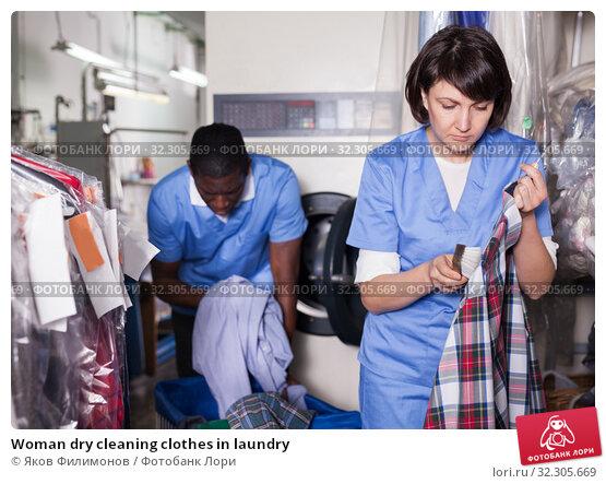 Купить «Woman dry cleaning clothes in laundry», фото № 32305669, снято 15 января 2019 г. (c) Яков Филимонов / Фотобанк Лори