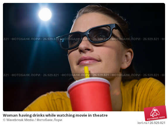 Купить «Woman having drinks while watching movie in theatre», фото № 26929821, снято 20 апреля 2017 г. (c) Wavebreak Media / Фотобанк Лори