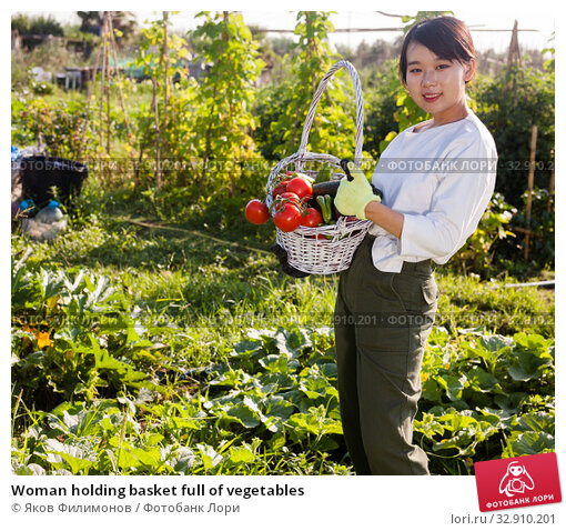 Woman holding basket full of vegetables. Стоковое фото, фотограф Яков Филимонов / Фотобанк Лори