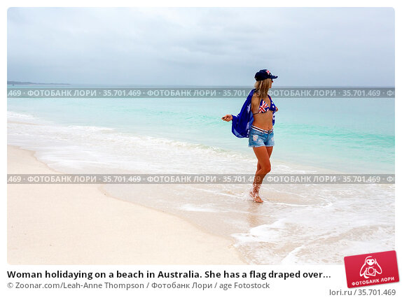 Woman holidaying on a beach in Australia. She has a flag draped over... Стоковое фото, фотограф Zoonar.com/Leah-Anne Thompson / age Fotostock / Фотобанк Лори