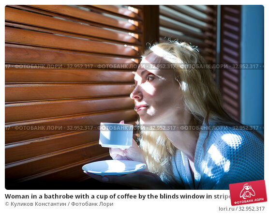 Woman in a bathrobe with a cup of coffee by the blinds window in striped light. Стоковое фото, фотограф Куликов Константин / Фотобанк Лори