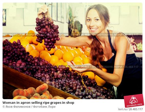 Купить «Woman in apron selling ripe grapes in shop», фото № 26483117, снято 10 февраля 2020 г. (c) Яков Филимонов / Фотобанк Лори