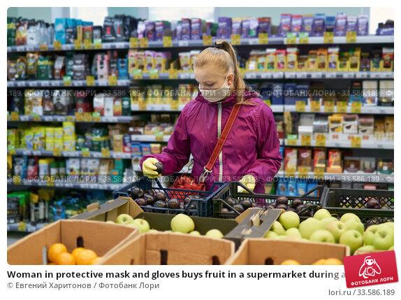 Купить «Woman in protective mask and gloves buys fruit in a supermarket during an outbreak of coronavirus», фото № 33586189, снято 17 апреля 2020 г. (c) Евгений Харитонов / Фотобанк Лори