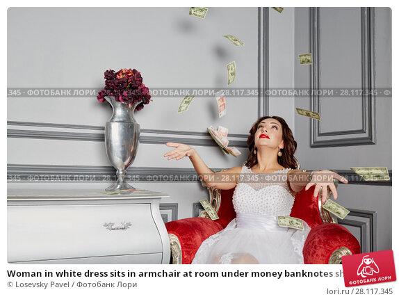 Купить «Woman in white dress sits in armchair at room under money banknotes shower», фото № 28117345, снято 14 ноября 2015 г. (c) Losevsky Pavel / Фотобанк Лори