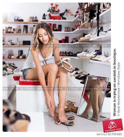 Купить «Woman is trying on sandals in boutique.», фото № 32170653, снято 17 августа 2017 г. (c) Яков Филимонов / Фотобанк Лори