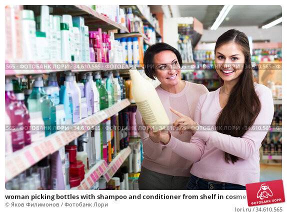 woman picking bottles with shampoo and conditioner from shelf in cosmetics store. Стоковое фото, фотограф Яков Филимонов / Фотобанк Лори
