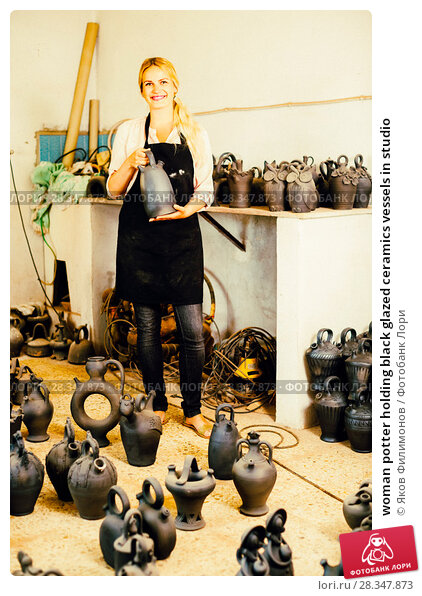 Купить «woman potter holding black glazed ceramics vessels in studio», фото № 28347873, снято 24 февраля 2019 г. (c) Яков Филимонов / Фотобанк Лори