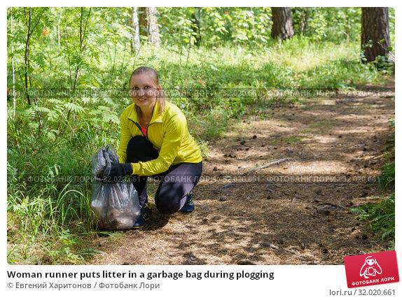 Купить «Woman runner puts litter in a garbage bag during plogging», фото № 32020661, снято 11 августа 2019 г. (c) Евгений Харитонов / Фотобанк Лори
