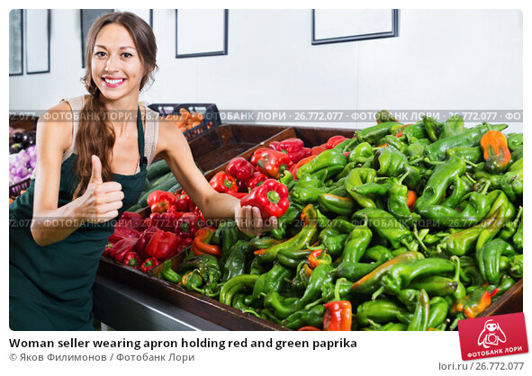 Купить «Woman seller wearing apron holding red and green paprika», фото № 26772077, снято 25 мая 2018 г. (c) Яков Филимонов / Фотобанк Лори