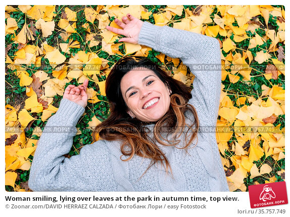 Woman smiling, lying over leaves at the park in autumn time, top view. Стоковое фото, фотограф Zoonar.com/DAVID HERRAEZ CALZADA / easy Fotostock / Фотобанк Лори
