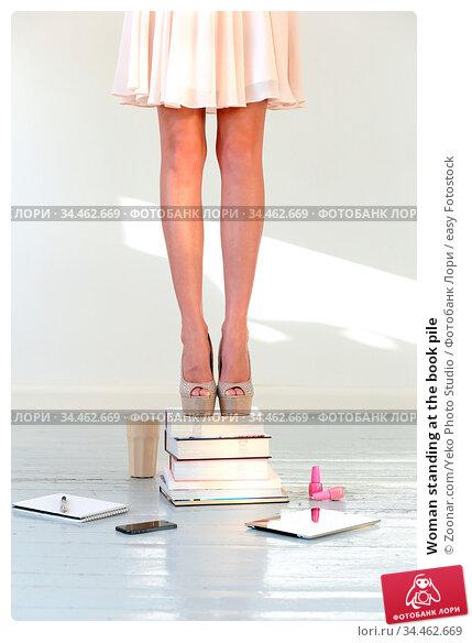Woman standing at the book pile. Стоковое фото, фотограф Zoonar.com/Yeko Photo Studio / easy Fotostock / Фотобанк Лори