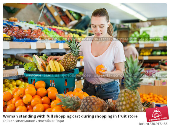 Купить «Woman standing with full shopping cart during shopping in fruit store», фото № 30917153, снято 27 апреля 2019 г. (c) Яков Филимонов / Фотобанк Лори