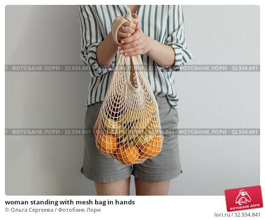 Купить «woman standing with mesh bag in hands», фото № 32934841, снято 1 июля 2019 г. (c) Ольга Сергеева / Фотобанк Лори
