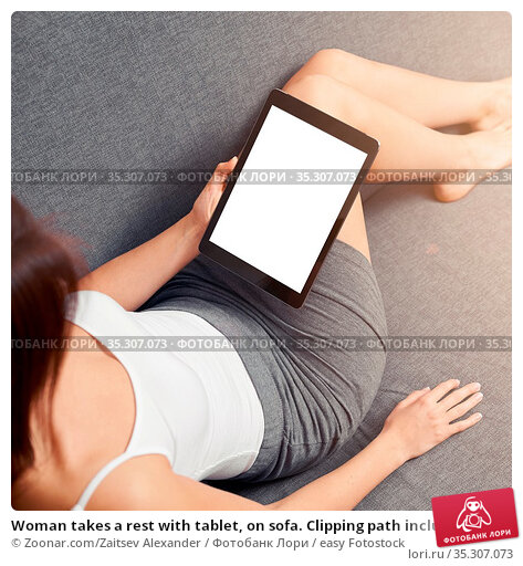 Woman takes a rest with tablet, on sofa. Clipping path included. Стоковое фото, фотограф Zoonar.com/Zaitsev Alexander / easy Fotostock / Фотобанк Лори