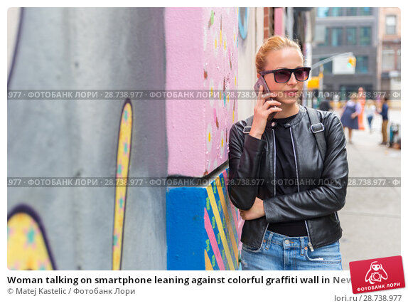 Купить «Woman talking on smartphone leaning against colorful graffiti wall in New York city, USA.», фото № 28738977, снято 21 июля 2018 г. (c) Matej Kastelic / Фотобанк Лори