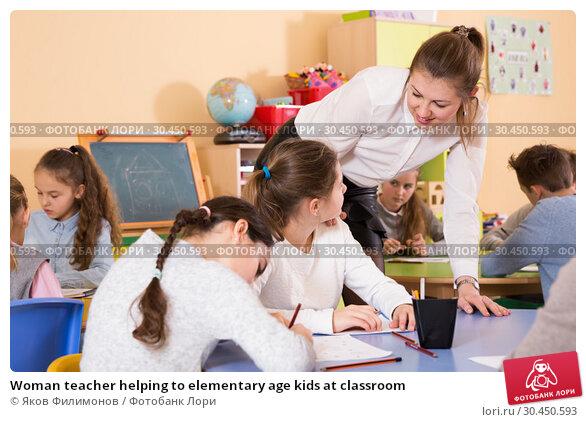 Woman teacher helping to elementary age kids at classroom. Стоковое фото, фотограф Яков Филимонов / Фотобанк Лори