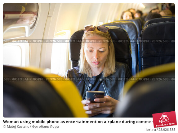 Купить «Woman using mobile phone as entertainment on airplane during commercial flight.», фото № 28926585, снято 21 августа 2018 г. (c) Matej Kastelic / Фотобанк Лори