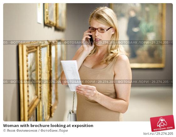 Купить «Woman with brochure looking at exposition», фото № 29274205, снято 22 сентября 2018 г. (c) Яков Филимонов / Фотобанк Лори