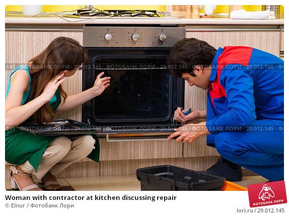Купить «Woman with contractor at kitchen discussing repair», фото № 29012145, снято 20 июня 2018 г. (c) Elnur / Фотобанк Лори