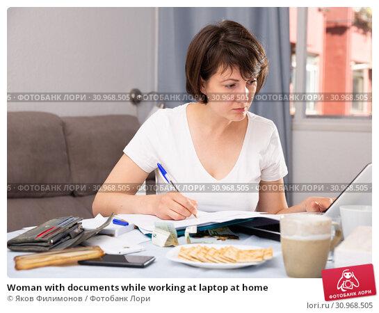 Купить «Woman with documents while working at laptop at home», фото № 30968505, снято 22 июля 2019 г. (c) Яков Филимонов / Фотобанк Лори