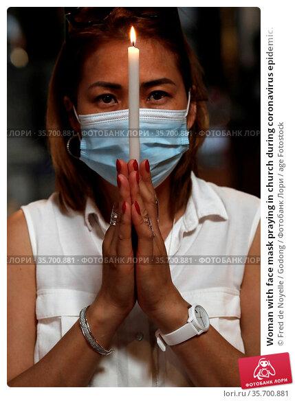 Woman with face mask praying in church during coronavirus epidemic. Стоковое фото, фотограф Fred de Noyelle / Godong / age Fotostock / Фотобанк Лори