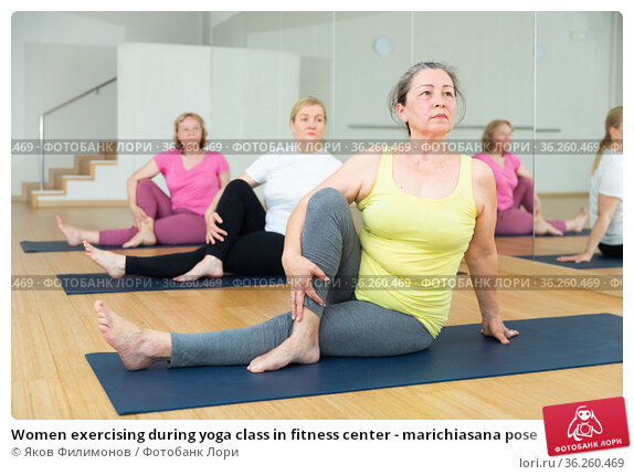 Women exercising during yoga class in fitness center - marichiasana pose. Стоковое фото, фотограф Яков Филимонов / Фотобанк Лори