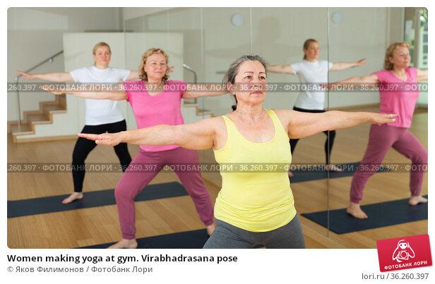 Women making yoga at gym. Virabhadrasana pose. Стоковое фото, фотограф Яков Филимонов / Фотобанк Лори