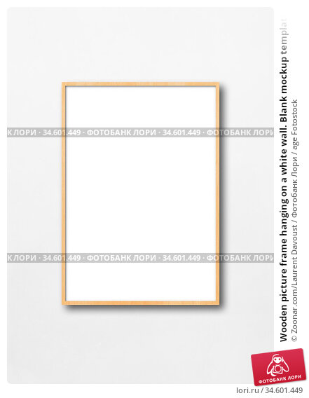 Wooden picture frame hanging on a white wall. Blank mockup template. Стоковое фото, фотограф Zoonar.com/Laurent Davoust / age Fotostock / Фотобанк Лори