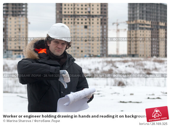 Купить «Worker or engineer holding drawing in hands and reading it on background of new apartment buildings and construction cranes on background. Architect engineer concept. Soft focus.», фото № 28169325, снято 16 сентября 2018 г. (c) Marina Sharova / Фотобанк Лори