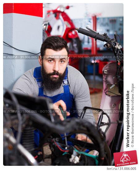 Купить «Worker repairing motorbike», фото № 31006005, снято 16 октября 2019 г. (c) Яков Филимонов / Фотобанк Лори