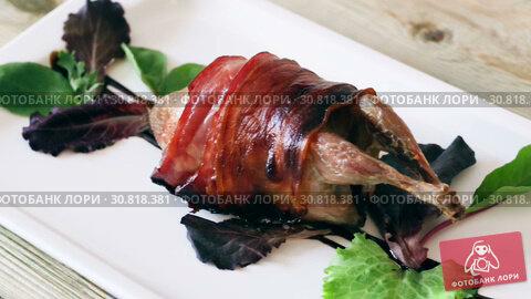 Купить «Wrapped in bacon baked quail served on plate seasoned with balsamic sauce», видеоролик № 30818381, снято 29 августа 2018 г. (c) Яков Филимонов / Фотобанк Лори