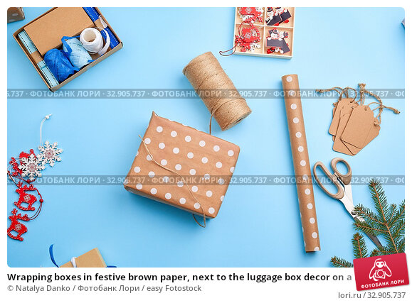 Wrapping boxes in festive brown paper, next to the luggage box decor on a blue background, top view. Christmas holiday concept. Стоковое фото, фотограф Natalya Danko / easy Fotostock / Фотобанк Лори
