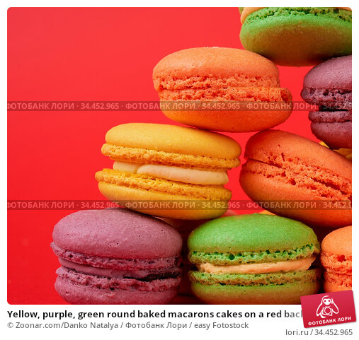 Yellow, purple, green round baked macarons cakes on a red background... Стоковое фото, фотограф Zoonar.com/Danko Natalya / easy Fotostock / Фотобанк Лори