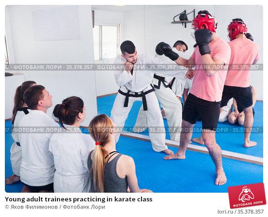 Young adult trainees practicing in karate class. Стоковое фото, фотограф Яков Филимонов / Фотобанк Лори