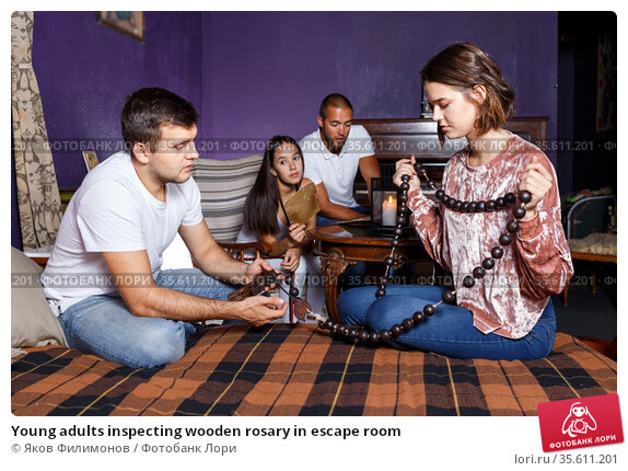 Young adults inspecting wooden rosary in escape room. Стоковое фото, фотограф Яков Филимонов / Фотобанк Лори
