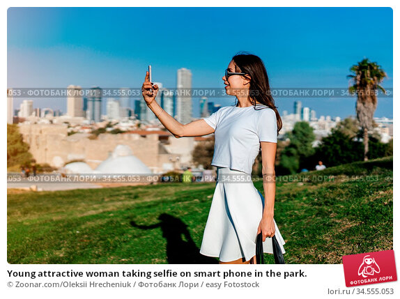 Young attractive woman taking selfie on smart phone in the park. Стоковое фото, фотограф Zoonar.com/Oleksii Hrecheniuk / easy Fotostock / Фотобанк Лори