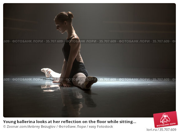 Young ballerina looks at her reflection on the floor while sitting... Стоковое фото, фотограф Zoonar.com/Anbrey Bezuglov / easy Fotostock / Фотобанк Лори