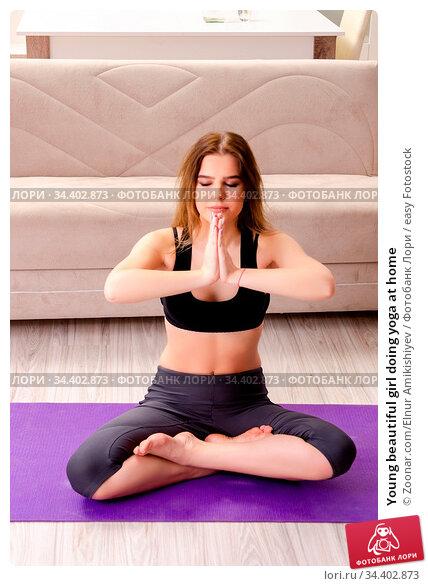 Young beautiful girl doing yoga at home. Стоковое фото, фотограф Zoonar.com/Elnur Amikishiyev / easy Fotostock / Фотобанк Лори