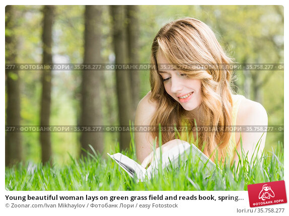 Young beautiful woman lays on green grass field and reads book, spring... Стоковое фото, фотограф Zoonar.com/Ivan Mikhaylov / easy Fotostock / Фотобанк Лори