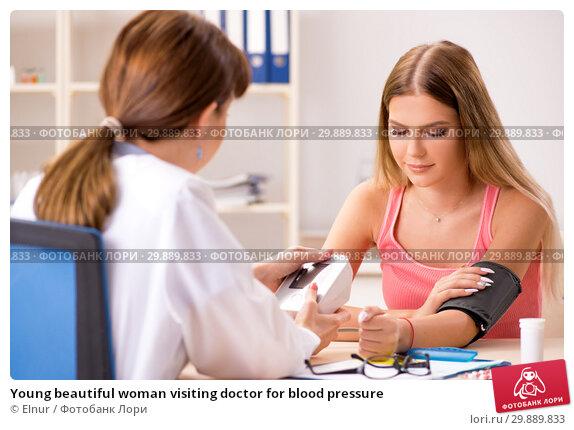 Купить «Young beautiful woman visiting doctor for blood pressure», фото № 29889833, снято 16 августа 2018 г. (c) Elnur / Фотобанк Лори