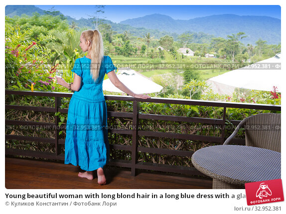 Young beautiful woman with long blond hair in a long blue dress with a glass of sparkling wine half a turn and looks at the tropical nature. Стоковое фото, фотограф Куликов Константин / Фотобанк Лори