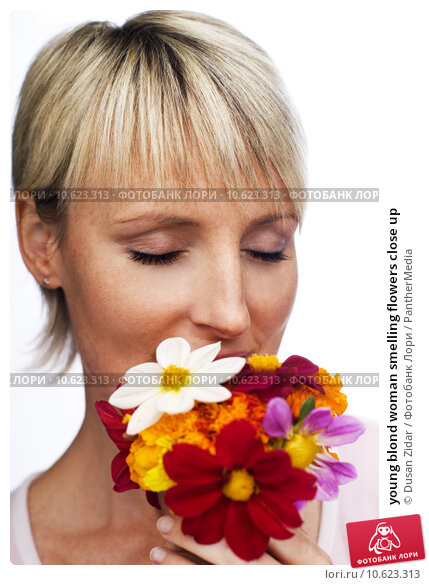 young blond woman smelling flowers close up. Стоковое фото, фотограф Dusan Zidar / PantherMedia / Фотобанк Лори