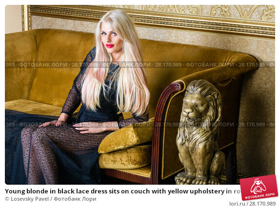 Купить «Young blonde in black lace dress sits on couch with yellow upholstery in room», фото № 28170989, снято 20 ноября 2015 г. (c) Losevsky Pavel / Фотобанк Лори