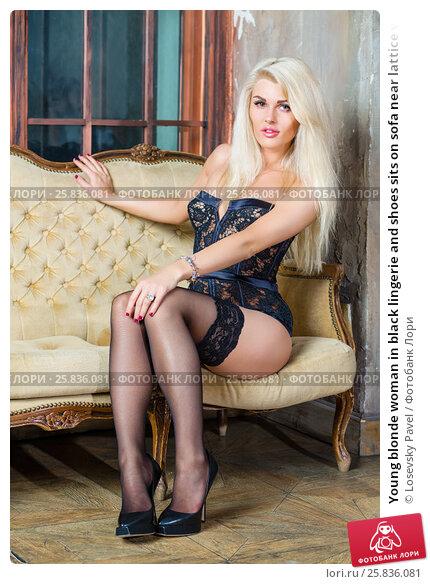 Купить «Young blonde woman in black lingerie and shoes sits on sofa near lattice window in room», фото № 25836081, снято 17 сентября 2015 г. (c) Losevsky Pavel / Фотобанк Лори