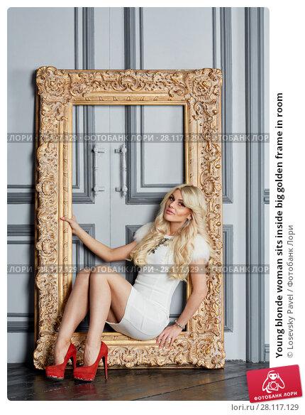 Купить «Young blonde woman sits inside big golden frame in room», фото № 28117129, снято 14 ноября 2015 г. (c) Losevsky Pavel / Фотобанк Лори