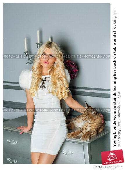 Купить «Young blonde woman stands leaning her back on table and strocking lynx cub», фото № 28117113, снято 14 ноября 2015 г. (c) Losevsky Pavel / Фотобанк Лори