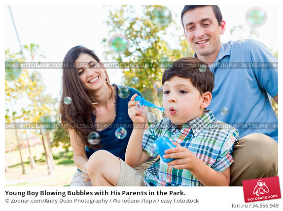 Young Boy Blowing Bubbles with His Parents in the Park. Стоковое фото, фотограф Zoonar.com/Andy Dean Photography / easy Fotostock / Фотобанк Лори