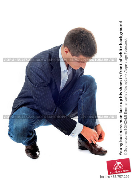 Young business man lace up his shoes in front of white background. Стоковое фото, фотограф Zoonar.com/BONZAMI Emmanuelle / age Fotostock / Фотобанк Лори