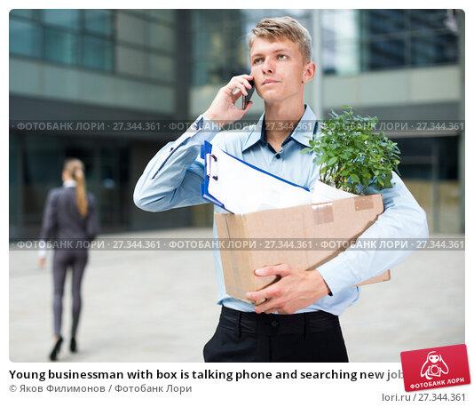 Купить «Young businessman with box is talking phone and searching new job», фото № 27344361, снято 15 июля 2017 г. (c) Яков Филимонов / Фотобанк Лори